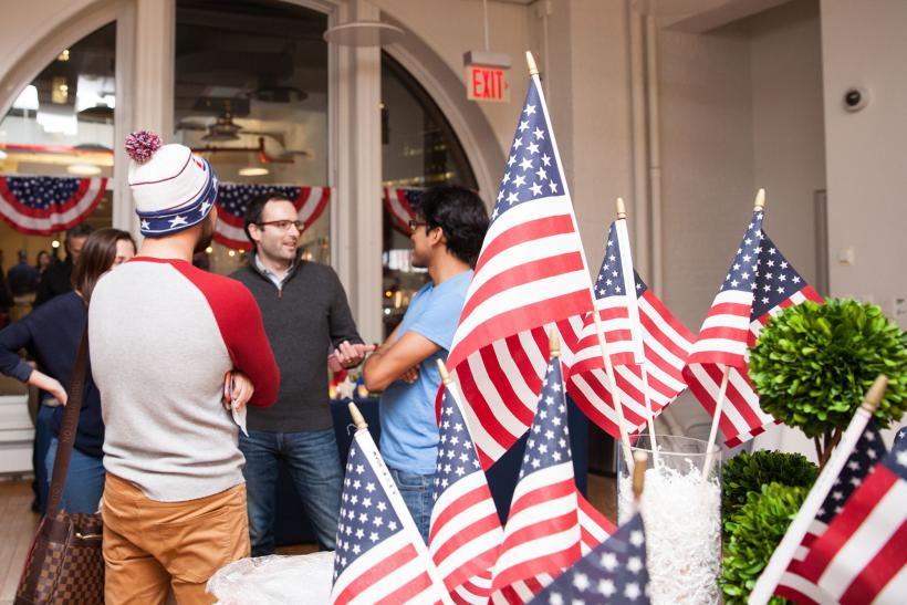 People in conversation with each other + American flag decoration