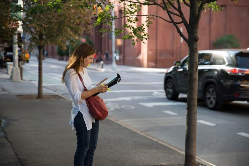 Person standing on street with notepad and pen in hand