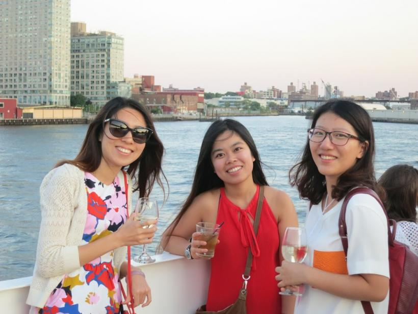 Group photo, people smiling with drinks in hand and ocean in background