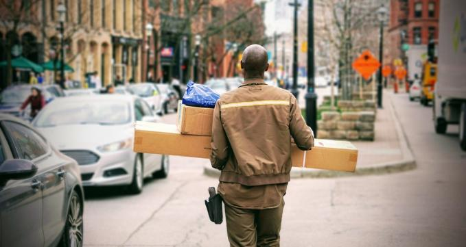 Delivery man with packages / Image via Unsplash